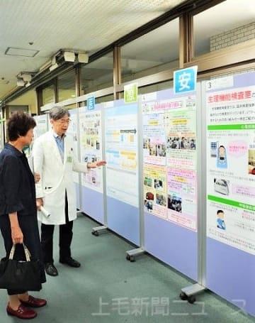 安全の取り組みを来院者に説明する小松教授(右)