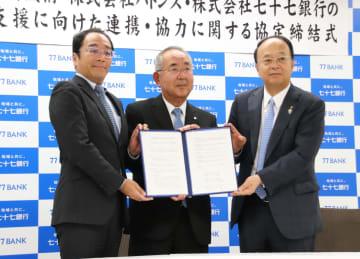 協定書を掲げる(左から)大山社長、伊本副理事長、津田常務