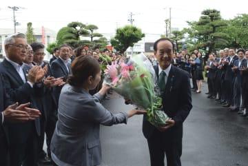 職員が出迎える中、初登庁して花束を受け取る小桧山氏