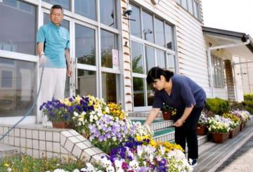 若宮小の閉校後も管理人として校舎の美化を守り、花の世話をする梶原さん(左)と秋山さん
