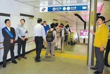 エスカレーター利用客に「歩かずに」と呼び掛ける市交通局職員ら=市地下鉄仙台駅