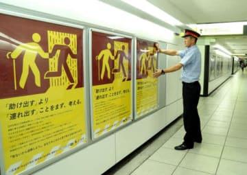 JR広島駅の地下通路にポスターを張る駅員
