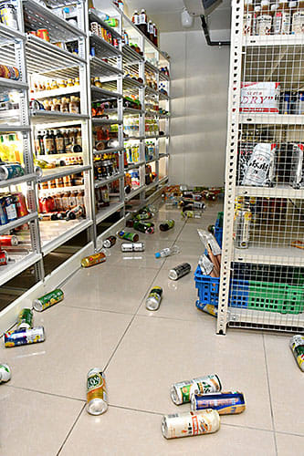地震で飲み物が棚から落ち、散乱したコンビニエンスストアの店内=18日午後10時57分、鶴岡市みどり町