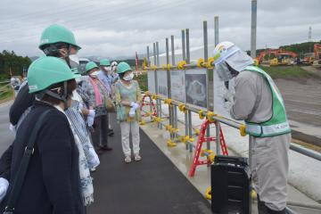 中間貯蔵施設の土壌貯蔵施設を見学する参加者。見学会は原則バスから降車できないが、地元住民だったことから特別に許可された=15日午前、福島県大熊町