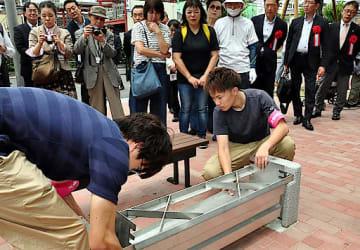 炊き出しができるようベンチをかまどに組み立てる学生ら=18日、大阪市東淀川区の大阪経済大