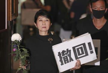 香港の立法会で「撤回!」と書かれたプラカードと白い花を手に会議に出席する民主派議員=19日(共同)