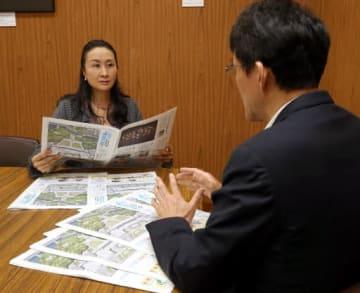佐藤編集局(右)から「学ぼうヒロシマ」の説明を聞く平川教育長