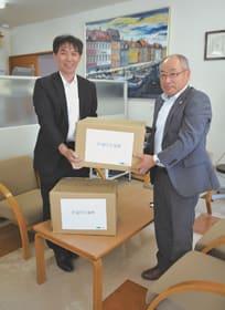 椎名常務理事に善意を手渡す作場上席調査役(左)