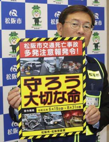 【交通死亡事故多発注意報のポスターを示す竹上市長=松阪市役所で】