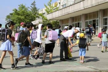 学校が再開し、登校する朝暘第六小学校の児童ら=20日午前、山形県鶴岡市