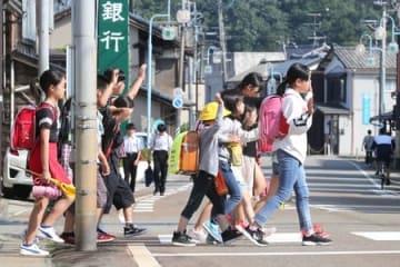 2日ぶりに学校が再開し、登校する岩船小の児童=20日午前7時30分すぎ、村上市岩船上町