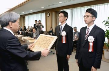 蒲島郁夫知事(左)から表彰状を受ける「東海大チャレンジセンター 阿蘇は箱舟プロジェクト」のメンバー=県庁