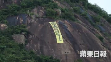A yellow banner atop Devil's Peak in Yau Tong reading 'Oppose bad police, protect students.' Photo: Apple Daily.