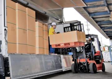 大型トラックに荷を積む運転手ら。長時間労働是正など、業界では働き方改革が急務となっている