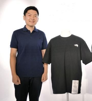 スパイバーの関山和秀社長とタンパク質素材の糸を使ったTシャツ=20日、東京都内