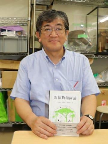 理系学生向けに出版した「新博物館園論」を手にする小林教授