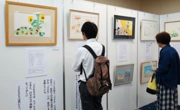 かこさんが描いた独特のタッチの原画に見入る来場者=川崎市中原区、エポックなかはら