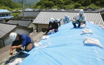 地震で被害を受けた瓦ぶきの屋根にブルーシートをかける人たち=20日、山形県鶴岡市