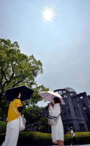 梅雨入りが遅れ、太陽が照りつける平和記念公園を散策する観光客たち(広島市中区)