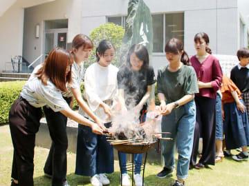 「ありがとう」と言葉を掛けながら筆を火にくべる学生たち=岐阜市太郎丸、岐阜女子大