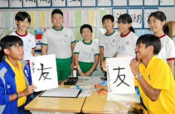 桜丘小の児童と書道で交流し、互いの作品を見せ合う「ASIAN ELEVEN」のチャナロング主将(右)ら