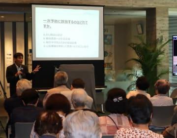 健康についてクイズを交えながら講演する高村教授(左奥)=国立長崎原爆死没者追悼平和祈念館