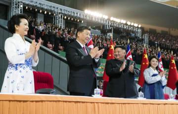 平壌のメーデースタジアムでマスゲームと芸術公演を観覧に訪れ、拍手する中国の習近平国家主席夫妻(左の2人)と北朝鮮の金正恩朝鮮労働党委員長夫妻=20日(新華社=共同)