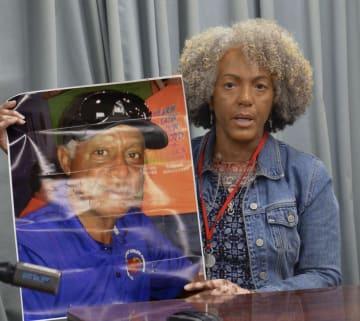 記者会見で亡くなった夫の写真を掲げるリディア・ジェラルドさん=21日午後、東京都千代田区