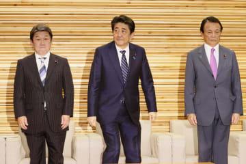 臨時閣議に臨む(左から)茂木経済再生相、安倍首相、麻生財務相兼金融相=21日午後、首相官邸