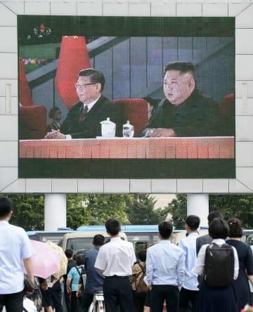 21日、平壌駅前で訪朝した中国の習近平国家主席(画面左)と北朝鮮の金正恩朝鮮労働党委員長のニュースを見る市民(共同)