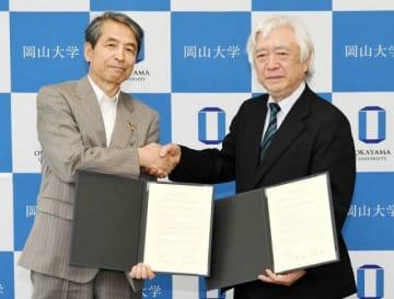 協定書に署名し握手をする槇野学長(左)と大原理事長