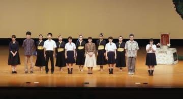 米軍戦闘機墜落事故の惨状を伝える舞台を終え、あいさつする北谷高校の生徒たち=21日午後、沖縄市民会館