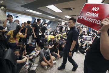 「逃亡犯条例」改正案の完全撤回などを求めて入管当局のビルを占拠するデモ隊=21日(共同)