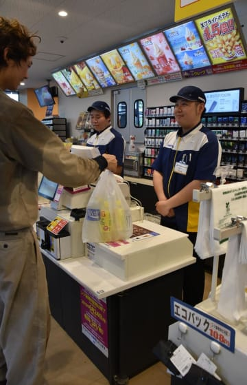 来週から有料化するレジ袋を受け取る利用客。レジ脇にはエコバッグも並ぶ=21日午後、千葉市美浜区のミニストップイオンタワー店