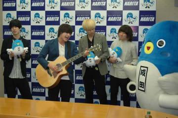 アコースティックギターを手に、メジャーデビューアルバム「FOREVER YOUNG」から「フォーエバーヤング」を披露する冨塚さん=21日、成田市役所