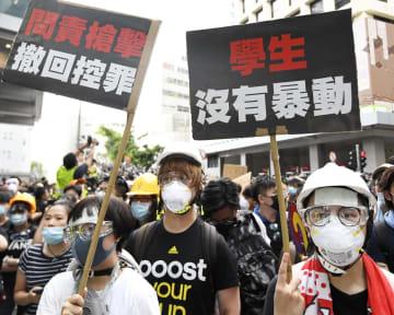 21日、香港の警察本部前で、「学生は暴動を起こしていない」などと書かれたプラカードを掲げて抗議するデモ隊(共同)
