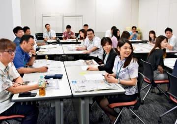 紙面の構成で記事の優先順位を学ぶ受講生ら=21日、那覇市泉崎の那覇ビジネスセンター