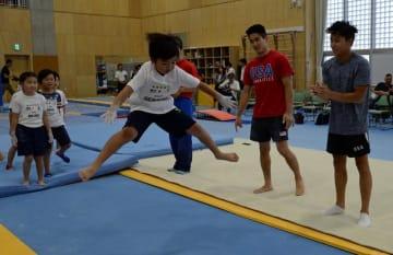 米国男子体操チームのゲンキ・スズキ選手(右から2人目)とユル・モルダウアー選手の指導を受け、トランポリンに挑戦する児童=22日、市立船橋高校第3体育館