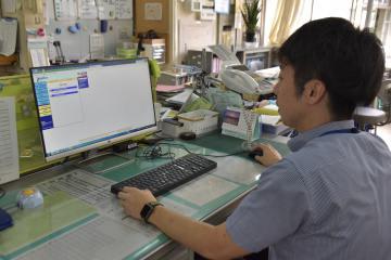 パソコンからインターネット上で学校の口座を確認する事務職員=古河市磯部