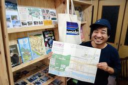 須磨区のまち育てサポーターとして3年間活動した角野史和さん。一番のお気に入りは「須磨のロゴ入りバッグ」(写真中央)だ=長田区久保町8