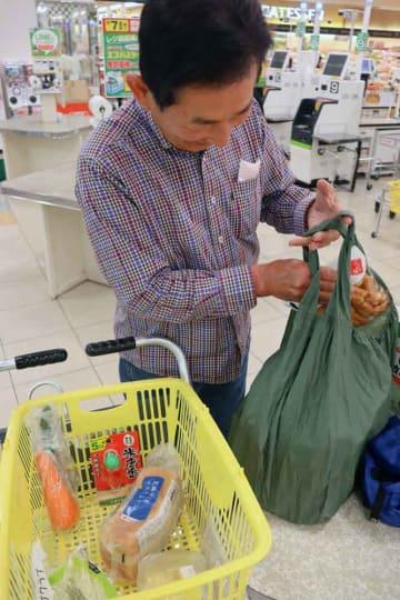 精算済みの商品を、持参したエコバッグに詰め替える男性(亀岡市荒塚町・スーパーマツモト荒塚店)