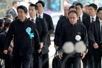 追悼式会場に到着したで安倍晋三首相(左)を硬い表情でエスコートする玉城デニー知事(右)=23日午後、糸満市・県平和祈念公園