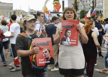 23日、モスクワで行われた集会で、当局により拘束された社会活動家の写真を掲げて解放を求める市民ら(共同)