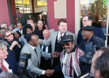 米ニューオーリンズでの記念式典で握手するバーソロミュー氏(中央左)とドミノ氏(中央右)=1999年12月10日(JENNIFER・ZDON/THE・TIMES―PICAYUNE提供、AP=共同)