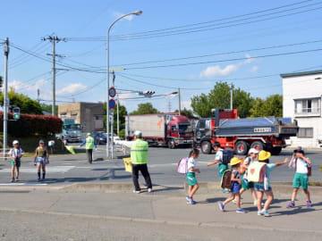 滝沢市土沢の交差点を通って下校する滝沢小の児童。道路は頻繁に大型トラックが行き交う