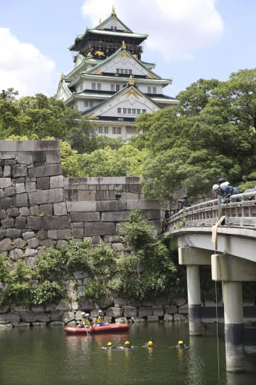 G20サミットの警備のため、大阪城公園の城の内堀で不審物がないか調べる大阪府警の警察官ら(下)=24日午前