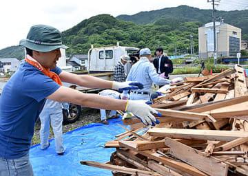 持ち込まれた廃材を指定のスペースに運ぶボランティア=23日午前9時26分、鶴岡市温海