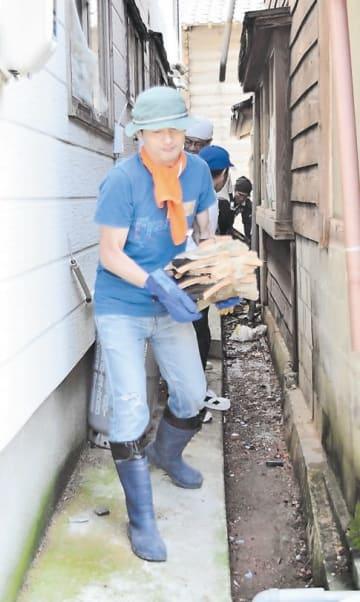 屋根瓦を運び出すボランティアら=23日、山形県鶴岡市小岩川