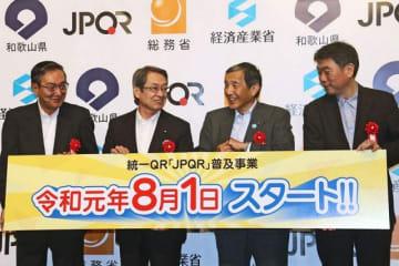 統一QRの普及に向けてPRした石田真敏総務相(左から2人目)や仁坂吉伸知事(右から2人目)ら=和歌山県白浜町で