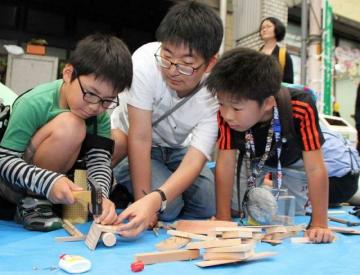 吉備国際大生(中央)に教わり、木工に挑戦する児童